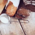 Baguette de bain, pain tranché, tamis avec farine déposé sur une planche de bois