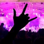 Main levée dans une foule devant une scène éclairée en rose